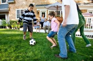 Child playing soccer with family