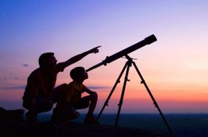 Father and son getting the best backyard views while stargazing