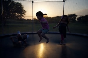 Children jumping on outdoor trampoline with safety net