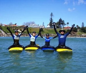 Four people sitting on stand up paddle boards with their arms raised