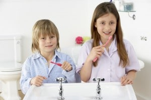 Siblings Brushing Teeth Together at Sink