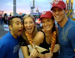 Two couples eating jumbo corn dogs at the fair