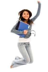 Happy female college student jumping with books in her hands