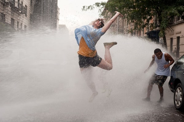Guy dancing in the street in the water from an open fire hydrant