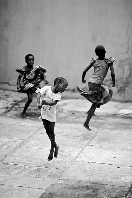 Three small children dancing on the street