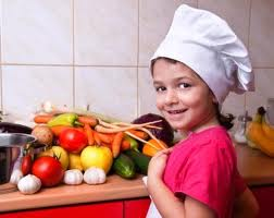 Young girl with several vegetables on the counter