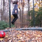 Lilybelle bouncing on her AlleyOOP outdoor trampoline in the fall