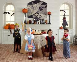 Four children in Halloween costumes with decorated room