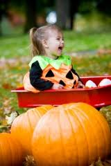 Baby girl in pumpkin costume in red wagon with large pumpkins in front of her