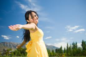 Woman in dress on sunny day feeling healthy and happy