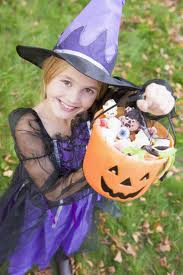Girl in Halloween witch costume with candy in her pumpkin basket