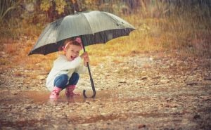 Girl with umbrella and fun ideas for kids on rainy days