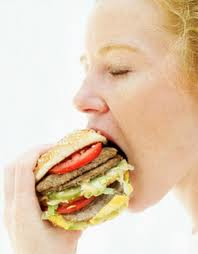 Woman overeating a large two patty burger