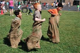 Three boys in a potato sack race
