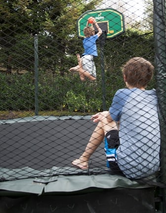 two children inside a trampoline, one watching, the other dunking a basketball