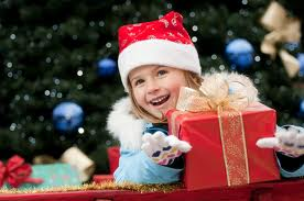 Child receiving wrapped Christmas presents by Christmas tree