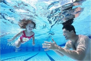 Young girl swimming underwater in the pool with her father