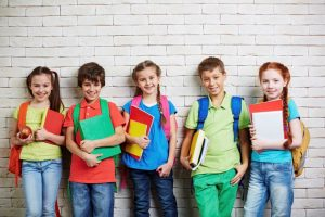 Children holding books with backpacks on