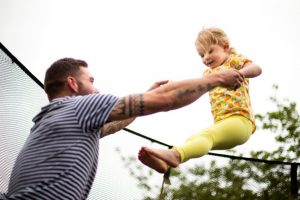 Father bouncing his child on a trampoline