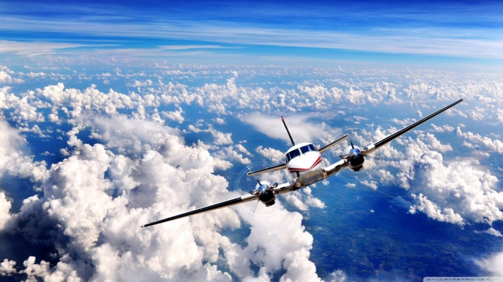 Twin engine propeller airplane flying in blue skies above the clouds