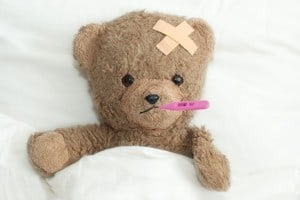 Sick teddy bear with thermometer in mouth and bandaid on head