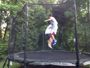 Kids jumping on trampoline with safety net