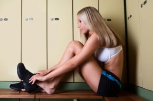 Woman in gym locker room getting dressed for workout success