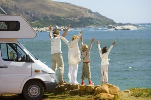 Family in front of RV doing travelcise at the ocean