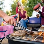 People barbequing meat on a grill outdoors