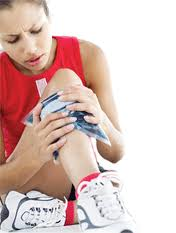 Female athlete icing her knee after an injury