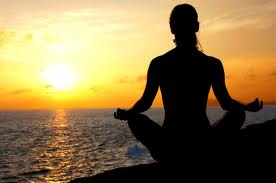 Woman meditating on a rock next to the ocean at sunset