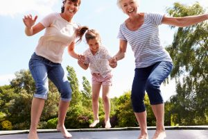 Girl playing outdoor trampoline games with family