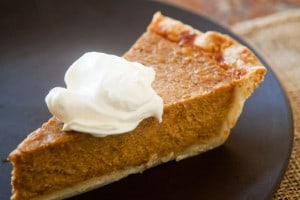 Slice of pumpkin pie with a dollop of whip cream